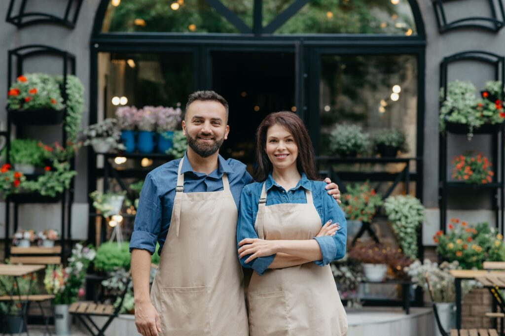 Owners of flower shop near showcase outdoor